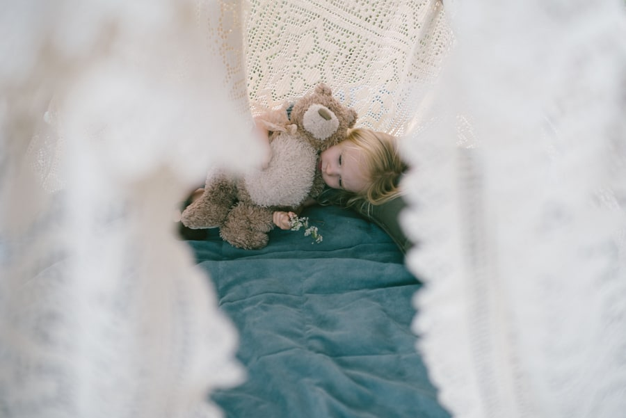 girl laying under tent with teddy bear